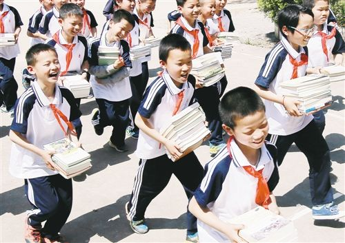 Students from a primary school in An County in southeast China's Jiangxi Province hold books donated to them by China's Publishers Association on April 14, 2017.[Photo: people.com.cn]