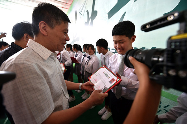 Graduating students perform a duet together and other students and teachers look on at the Linfen Red Ribbon School for students with AIDS on May 26, 2017. [Photo: Xinhua]