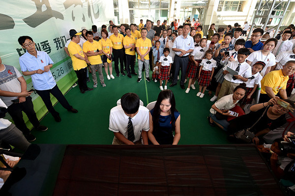 A student is awarded his diploma at the graduation ceremony for the Linfen Red Ribbon School for students with AIDS on May 26, 2017. [Photo: Xinhua]