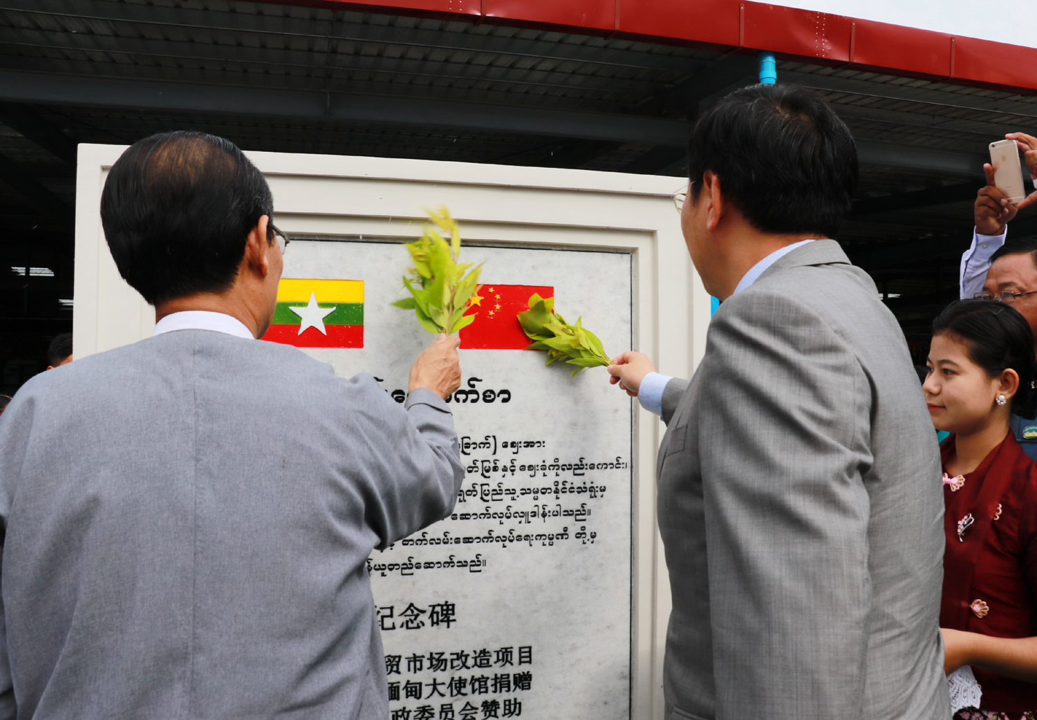 Chinese Ambassador to Myanmar, Hong Liang, and Chairman of Nay Pyi Taw Council, Dr. Myo Aung, reveal a stone monument for the rebuilt Thapyaygone Market on May 27, 2017. [Photo: China Plus/Tu Yun]