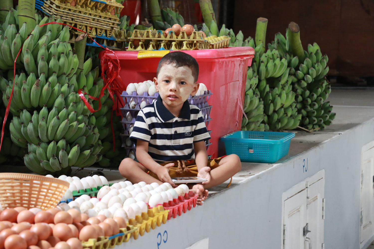 A boy sits on the commodity platform in the new market on May 27, 2017. [Photo: China Plus/Tu Yun]