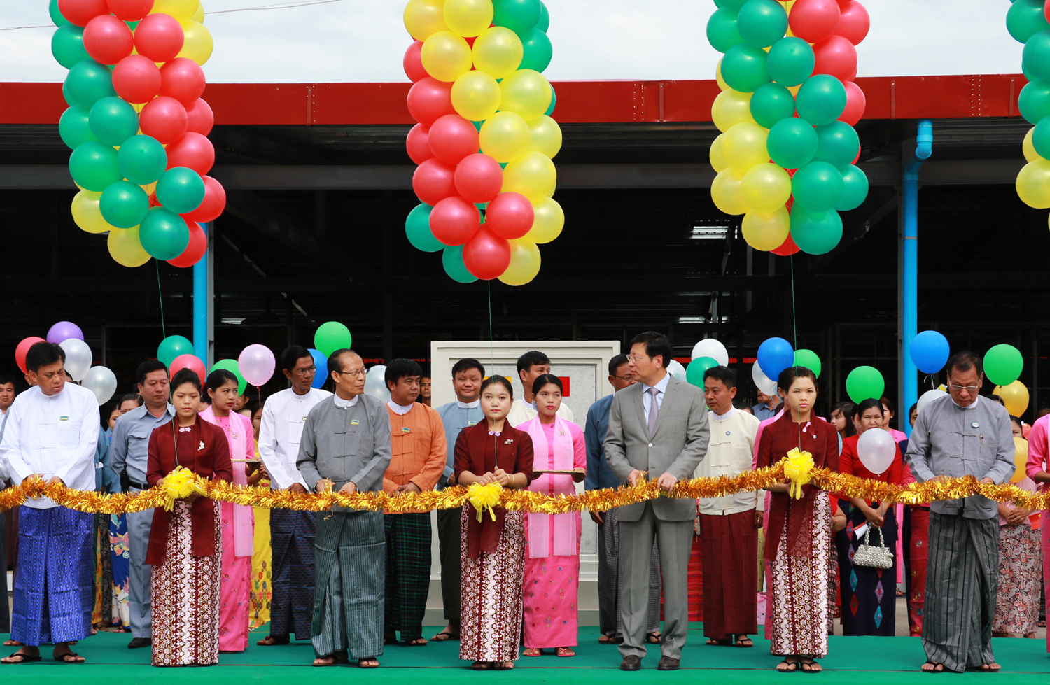 Chinese Ambassador to Myanmar, Hong Liang (third from right), and Chairman of Nay Pyi Taw Council, Dr. Myo Aung (third from left), cut the ribbon at the handover ceremony of the rebuilt Thapyaygone Market on May 27, 2017. [Photo: China Plus/Tu Yun]