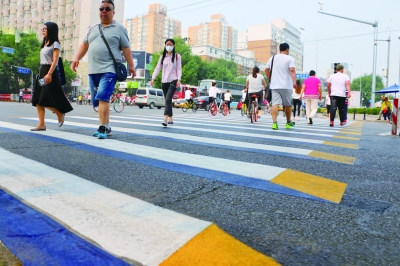 A 3D crosswalk painted in white, blue and yellow at a crossing in Beijing. [Photo: Legal Evening News]